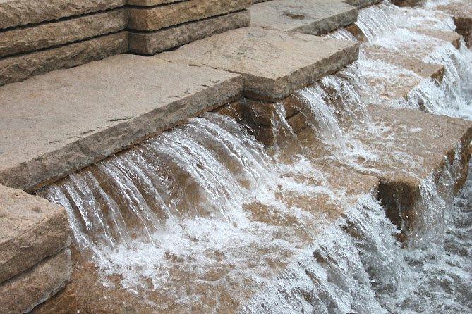 水流从由下至上第三层石块的缝隙中流出,出水口距离地面的高度目测是大约2英尺。(Photocredit: 周啸